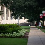 Students with masks walk on teh Quad in front of Gorgas Library.