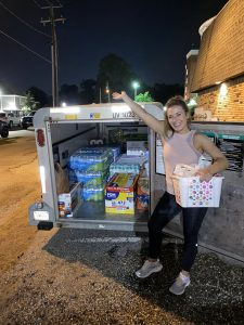 Girl stands in front of U-Haul full of supplies for those impacted by Hurricane Laura.