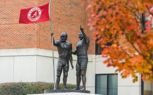 A statue of football players holding an Alabama flag outside of Bryant-Denny Stadium.