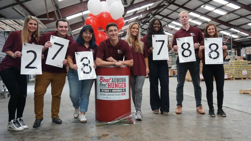 Students stand in front of a barrel at the 2019 Beat Auburn Beat Hunger food and fund drive result day.