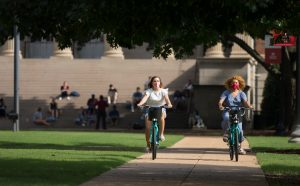 Two students riding bikes on campus.