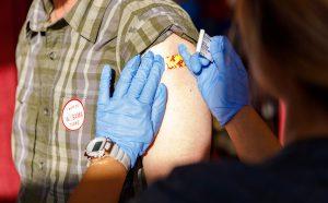 A nurse putting a band aid on a person following a flu shot.