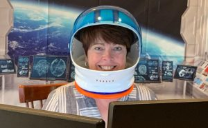 Kim Armstrong wearing a space helmet in front of a Zoom background showing earth from space