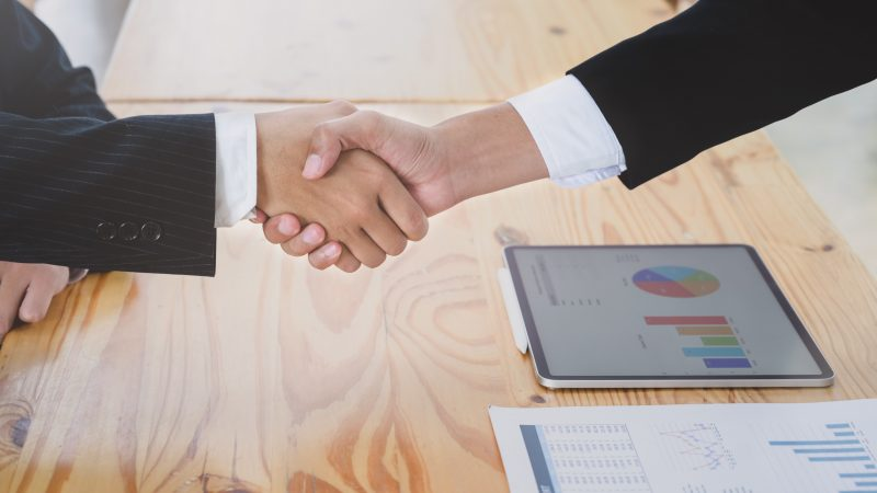 Two hands shake over a wooden table with business charts laying on top.
