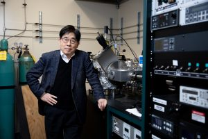 A man stands in an electrical engineering lab for a portrait.