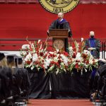 Dr. Bell speaks to students on stage at summer commencement.