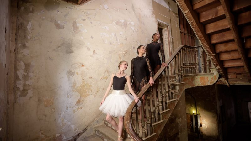 Three ballet dancers in a stairwell of Bryce Main.