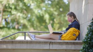 A female student wearing a mask works outside on her computer.