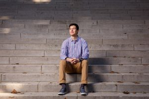 A man sits on concrete stairs for a portrait.