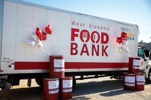 A display of the West Alabama Food Bank collection truck and barrels.