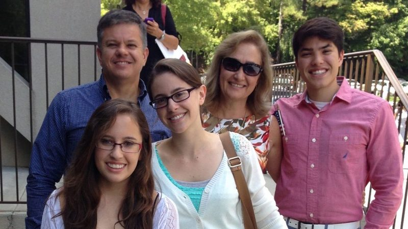The Carrasquilla family (Laura in front with blue dress, Tatiana with green dress, Juan with salmon shirt in the back, their father Carlos in the blue shirt and mom Liliana wearing sunglasses) at their U.S. citizen naturalization ceremony in 2016.