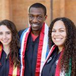 Three students wearing graduation gowns.