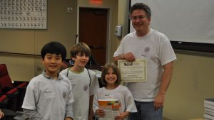 Three elementary students pose with Dr. Jeff Gray at the first UA robotics competition in 2011.