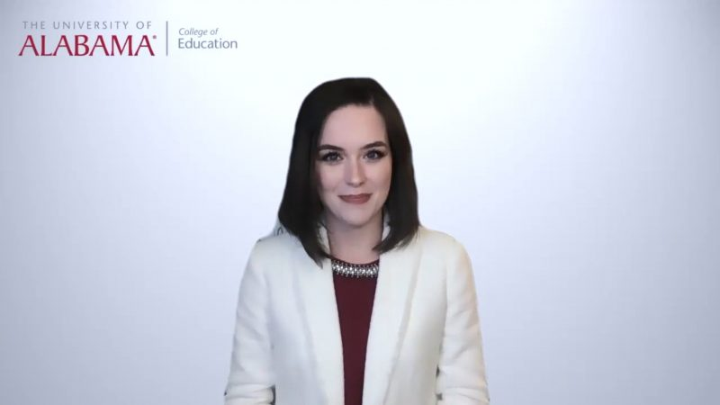 A woman in business attire speaks in front a white background.