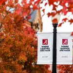 """two lampost banners reading """"Where legends are made"""" set against bright-color autumn leaves in the trees"""