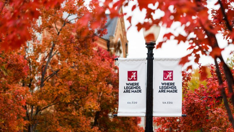 "two lampost banners reading ""Where legends are made"" set against bright-color autumn leaves in the trees"
