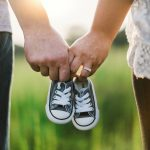 Couple holding hands with baby shoes