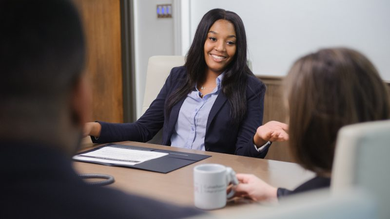 Female student sitting at a conference table talking to other students.