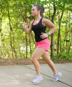 A jogger in shorts and a tank top runs on a path outdoors