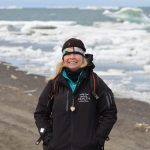 Leigh Mayberry stands in front of an icy Arctic Ocean.