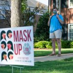 A UA student stands behind a mask sign on campus.
