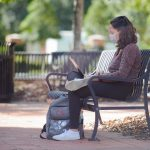 A student sets on a bench working on her computer on the UA campus.
