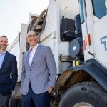Two men in suits pose in front a Tuscaloosa garbarge truck.