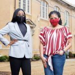 Two UA students in masks stand in front of B.B. Comer Hall.
