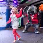 A young girl dancing with Big Al at a 2017 dance marathon