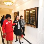 Autherine Lucy Foster in a red suit walks down the hall during the Malone Hood Plaza dedication in 2010