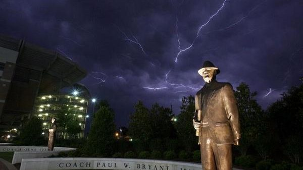 Lightning flashes in the sky over the Paul W. Bryant Statue on the Walk of Champions