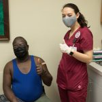 A nursing student and patient giving a thumbs up after the patient received the coronavirus vaccine