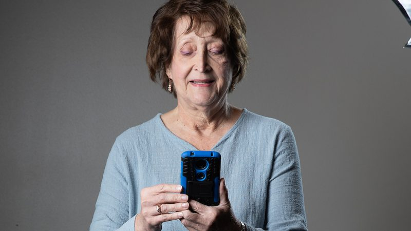 A woman looking down at her smartphone