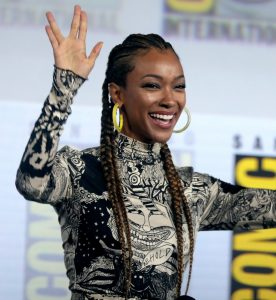 Sonequa Martin Green smiles and holds up the Vulcan hand signal to a crowd at Comic Con