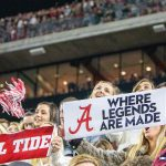 UA students hold signs in the stands of a football game.