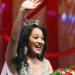Miss Tiara Pennington holds a bouquet of flowers an waves to the crowd after being name Miss Alabama 2019