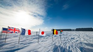 International flags fly around the South Pole on the ice with a research facility in the background.