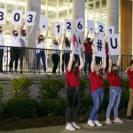 A group of students holding signs that reveal the total of money raised over the past year.