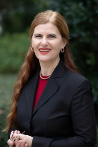 A portrait of a woman in a suit outside.