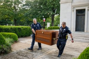 Two police officers carry a large box.