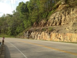 A road stretches in front of a rock outcropping beside it.