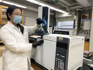 A scientist in a white lab coat and face mask works in a lab with equipment.