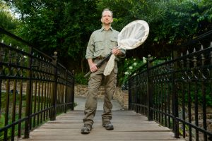 Dr. John Abbott standing outside holding a large net