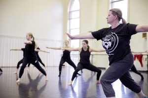 A professor teaches her students dance.