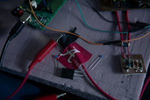 Circuits and electrical wires are connected with UA-themed tape.