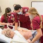 Four nursing students training on a simulator in a lab