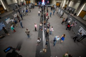 A room of people viewed from above as they examine research poster presentations.