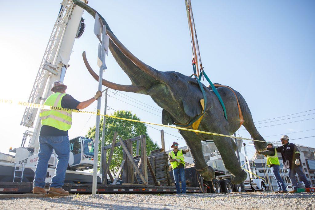 bronze elephant statue hangs from a crane.