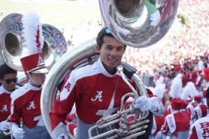 A college student holding the tuba.