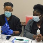 twp nurses in face masks examine a vial while sitting at a table